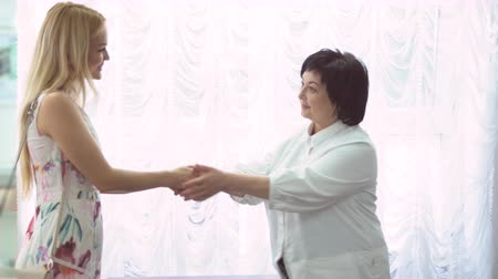 проверка : Satisfied young woman customer bids farewell to the doctor in cosmetic salon