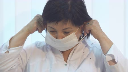 surgical mask : Close-up middle-aged woman doctor wearing face mask for procedures and operations Stock Footage