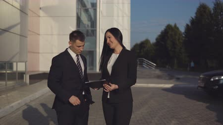продавщица : Business meeting. Young beautiful businesswoman talks and shows documents to young male employee outdoors against backdrop of business center