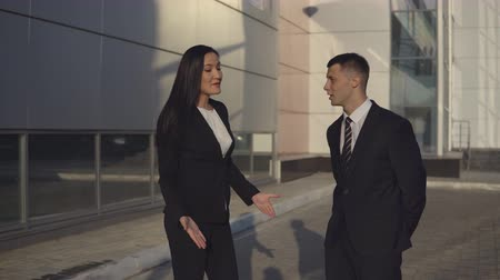 хулиган : Conflict of businesspeople. Businessman and businesswoman in formal suits argue about something by swinging their arms and shouting something outdoors Стоковые видеозаписи