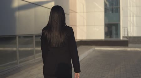 sexy heels : back view of young beautiful successful businesswoman in black suit walks down the street along large business center