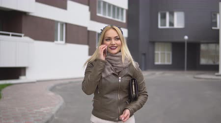 alluring : Cute young positive blonde with tiara and with handbag talking on smartphone while walking around the city standing on background of building