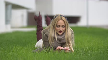 портфель : young blonde girl with on her head looking into the camera and lying on green lawn against the background of blurry building. Стоковые видеозаписи