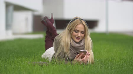 портфель : Young cute blonde girl lies in green lawn and looks at smartphone
