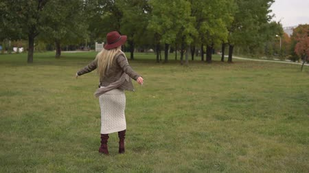 wool : Positive beautiful blonde in warm autumn clothes and hat turns around opening her hands to the sides while walking in the park, slow motion