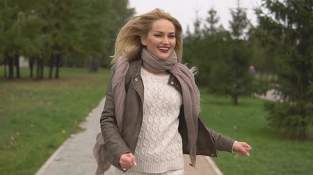 başörtüsü : Portrait of beautiful positive blond woman running along the street and joyfully raising her hands upwards during walk in the autumn park Stok Video