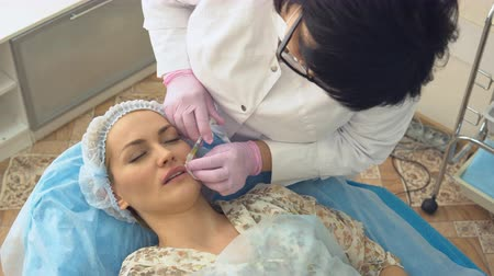 zmarszczki : Young woman lies on couch with doctor during lip injections and wrinkles her face from pain