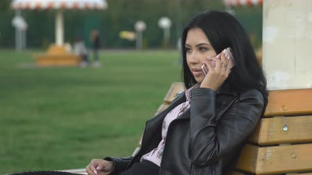 nadrág : Cute young brunette girl in leather jacket talking to someone on smartphone sitting on bench while walking in the park Stock mozgókép