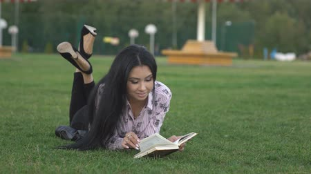 novel : girl lying on green lawn in park and reading book, copyspace