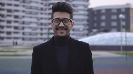 cheerfulness : Portrait of young attractive businessman in glasses and looking at the camera. Man smiling and making thumbs up, slow motion. Stock Footage