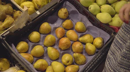 pears : hands of a girl choosing pear at fruit vegetable supermarket.