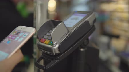 charged : Girl buying food and paying with his phone. Wireless payment concept. Supermarket store Stock Footage