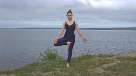 позы : Yoga attractive girl in sportswear pose against lake. Yogi training, outdoor meditation on river shore, healthy lifestyle Стоковые видеозаписи