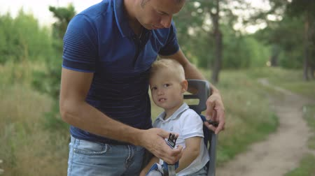 три человека : Little boy in child bike seat, father wear a seat belt. Male cyclist with son, cycling in the forest. Man with kid walks on cycle in park