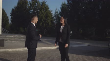 shaking hand : Informal business meeting. Young businessman and pretty businesswoman greeting each other with handshake outdoors on sunny day Stock Footage