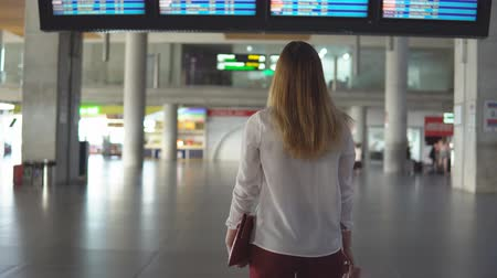 cancelado : Cute blonde girl in casual clothes is sad in an empty airport terminal and looks into the camera