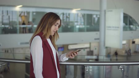 menetrend : young girl in elegant clothes stands and typing in the smartphone in the airport