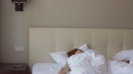 hate : Morning awakening. Young woman turns off the alarm clock on her smartphone lying in big bed Stock Footage