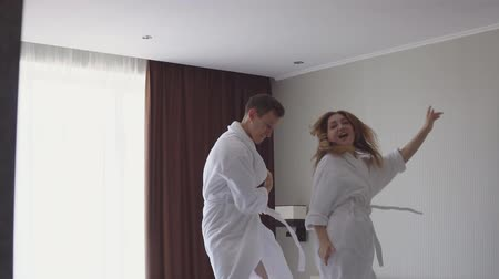 пуховое одеяло : Excited happy couple jumping and dancing on bed after arriving to hotel bed in beachside apartment. Стоковые видеозаписи