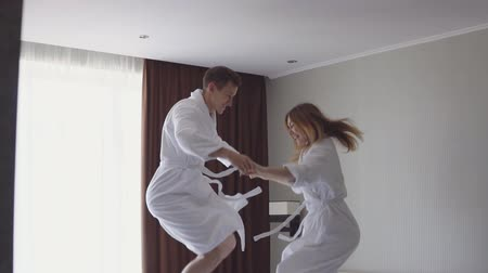 пуховое одеяло : Young couple jump up and down on a hotel bed