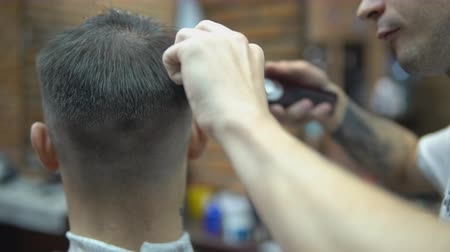 mistr : The hands of young barber making haircut to attractive man in barbershop.