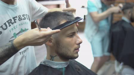 barber scissors : Confident man visiting hairstylist in barber shop
