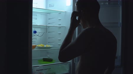 ataque : Hungry man is looking for food to eat in fridge at night. Unhealthy food concept