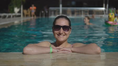 солнечные ванны : beautiful young girl in sunglasses swimming in an outdoor pool while on sunny summer day
