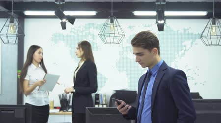 sorriso largo : Business concept. Young businessman in formal attire looks smartphone on background of two young female employees discussing work in the office Vídeos