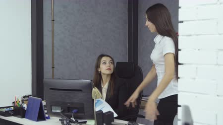 conflict : Conflict at work. Young woman boss in formal clothes throws the papers to her woman secretary - cursing about the mistake during working day at the office