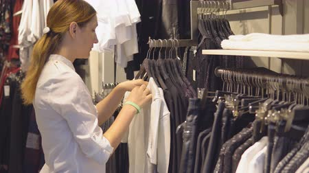 pitka : beautiful young girl chooses dresses in an elite boutique of womens clothing during shopping Dostupné videozáznamy