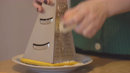 porcelana : Girl chopping cheese on a metal grater on a plate.
