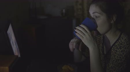 serial : young girl in bathrobe watching the movie at the computer and eating chips in night. Stock Footage