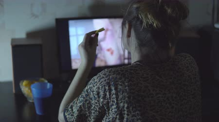 serial : young girl watching the movie at the computer and eating chips. Stock Footage