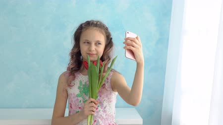 fragrances : Girl with a bouquet of tulips takes pictures of herself on the phone.