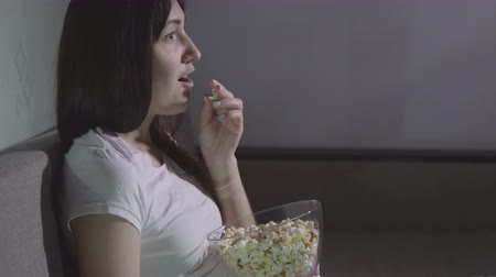 ilginç : Young beautiful woman alone watching a movie in the evening with popcorn. Stok Video