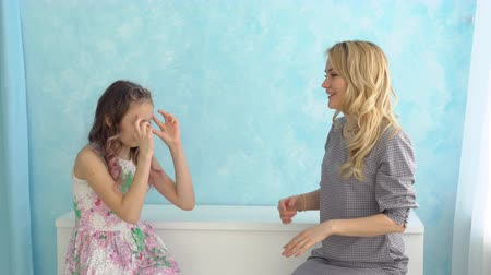 travessura : Mother and daughter are sitting next to each other and writhe faces against the blue wall. Vídeos