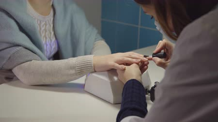 manicured hands : Nail care in the salon. Master applies gel-lacquer on the nails of a young woman.