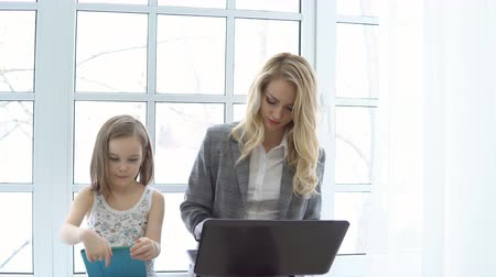 планшетный компьютер : Business mother with laptop and daughter sitting by the window. Стоковые видеозаписи