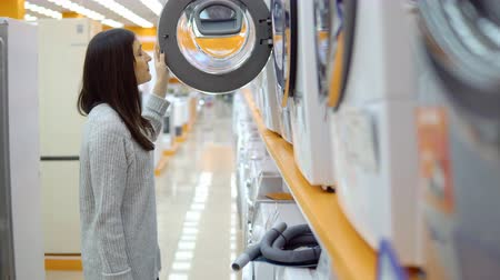 supermarket shelf : Household appliances store. A young woman chooses a washing machine.