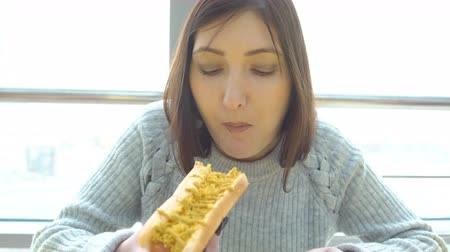 stuffing : Concept unhealthy food. Woman eats a hot dog at a fast food cafe.