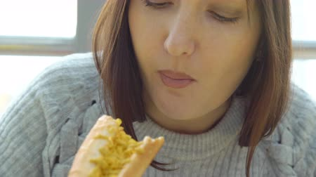 mustár : Concept unhealthy food. Woman eats a hot dog at a fast food cafe with an appetite, close up Stock mozgókép