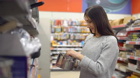 cserépedény : Young woman in a home-goods store chooses a saucepan. Stock mozgókép