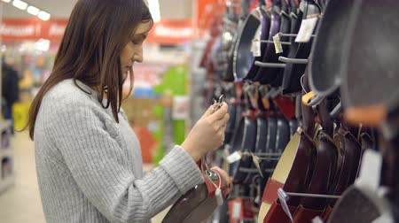 кухонная посуда : Young woman in a household goods store picks a frying pan.