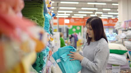 домохозяйка : Textile. A young woman chooses a towel in a store for home products.