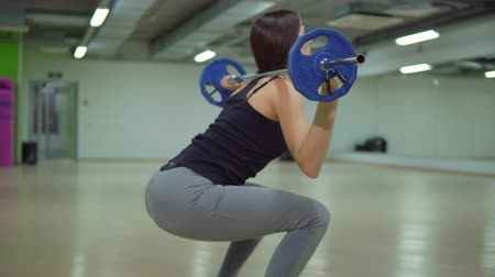 súlyzó : Beautiful brunette woman crouches with a barbell in the gym. Fitness concept. Stock mozgókép