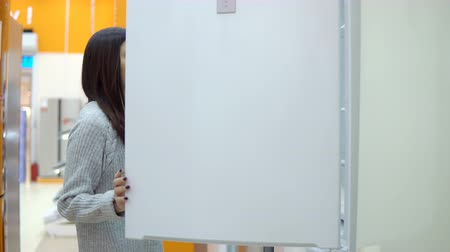mrazák : Brunette woman chooses a refrigerator in a home appliance store.
