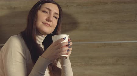 латте : Woman enjoys drinking hot fresh coffee from a paper cup.