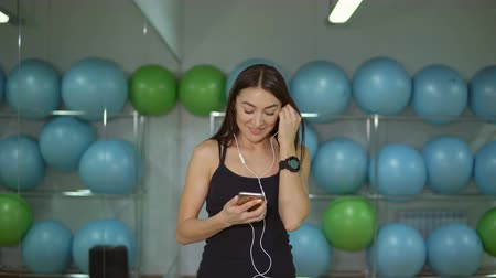 ouvir : Young woman in gym with headphones against background of gymnastic balls.