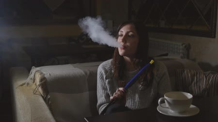 harmful : Young brunette woman in a cafe fires smoke from a hookah, slow motion